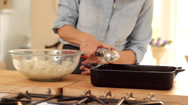 scooping biscuit dough onto casserole with an ice cream scooper
