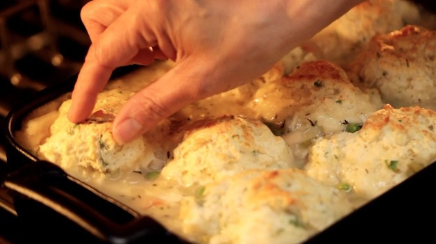 repositioning biscuits with fingers on top of a casserole in the oven