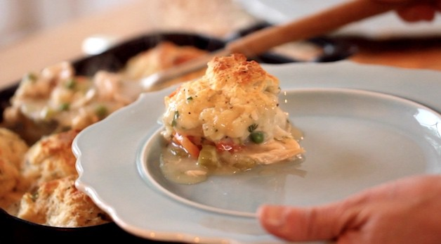 Spooning chicken and biscuit casserole serving on to a plate