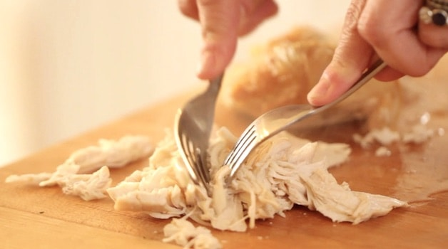 shredding cooked chicken breast on a cutting board with forks
