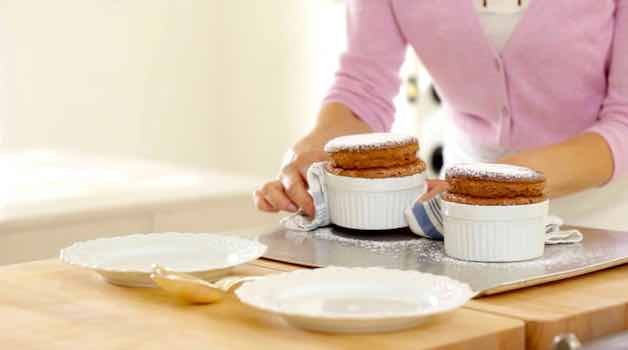 Placing fully baked chocolate souffles dusted with powdered sugar on a serving plate