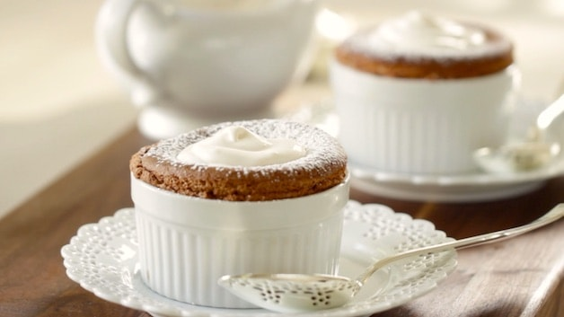 Two Chocolate Souffles on a table topped with whipped cream