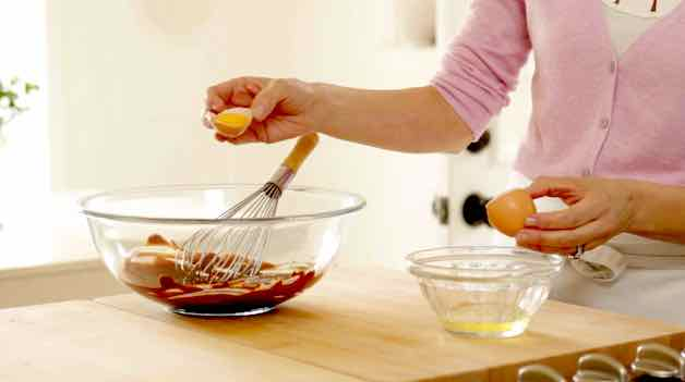Adding egg yolks to a chocolate base in a glass bowl