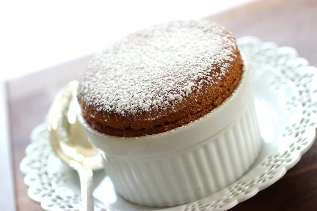 Chocolate Souffle in ramekin sitting on a white plate with silver spoon