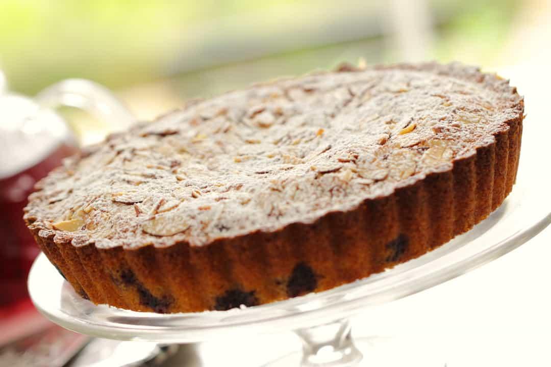 Blueberry Almond Tea Cake on a glass cake stand