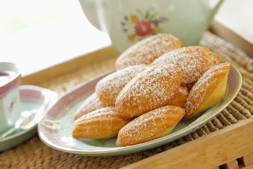 Easy Madeleine Recipe sitting on a plate, dusted with sugar
