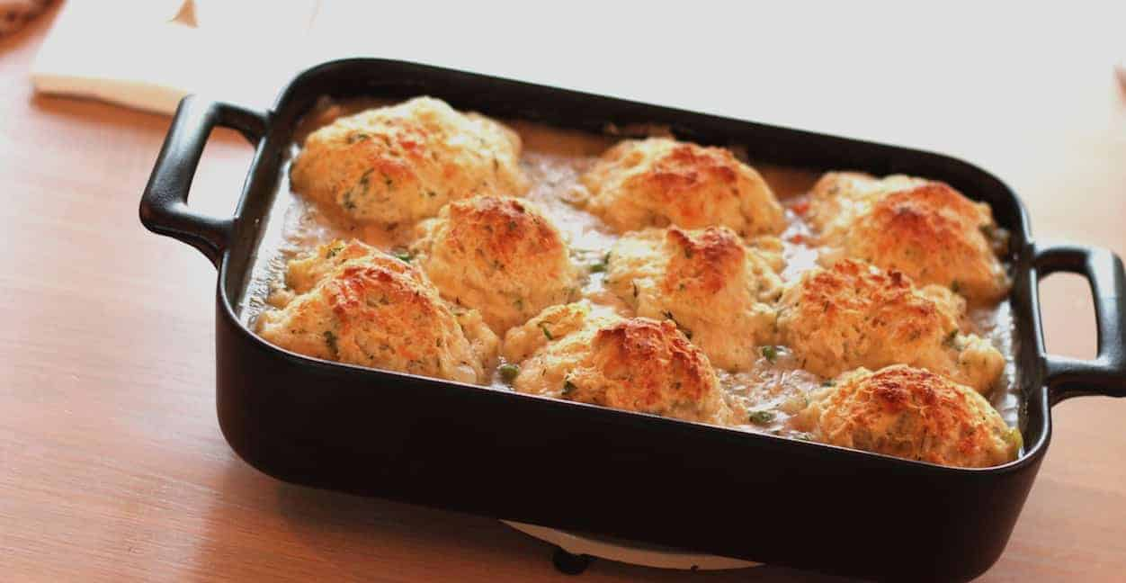 Chicken and Biscuits Recipe in a black baking dish on table