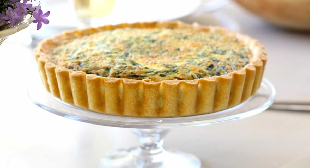 Spinach and cheese quiche on a glass cake stand
