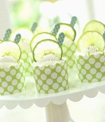 key lime cups served in green cupcake liners on a white cake plate