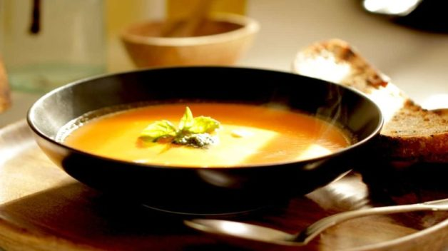 easy tomato soup recipe served in a large black bowl with fresh basil on top