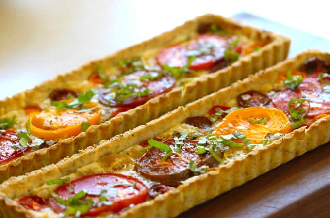 Tomato Tart Recipe baked and served on a dark wood surface