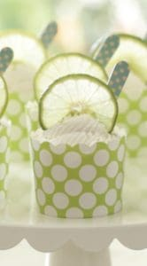 key lime cups served in a green cupcake liner with a wood blue spoon in