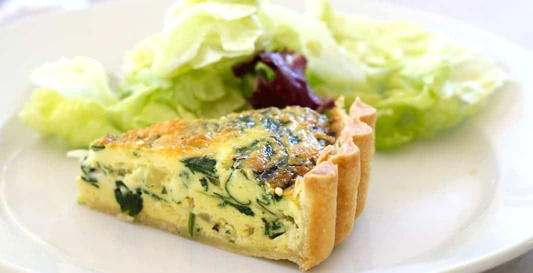 Slice of a quiche on a plate with a tossed salad