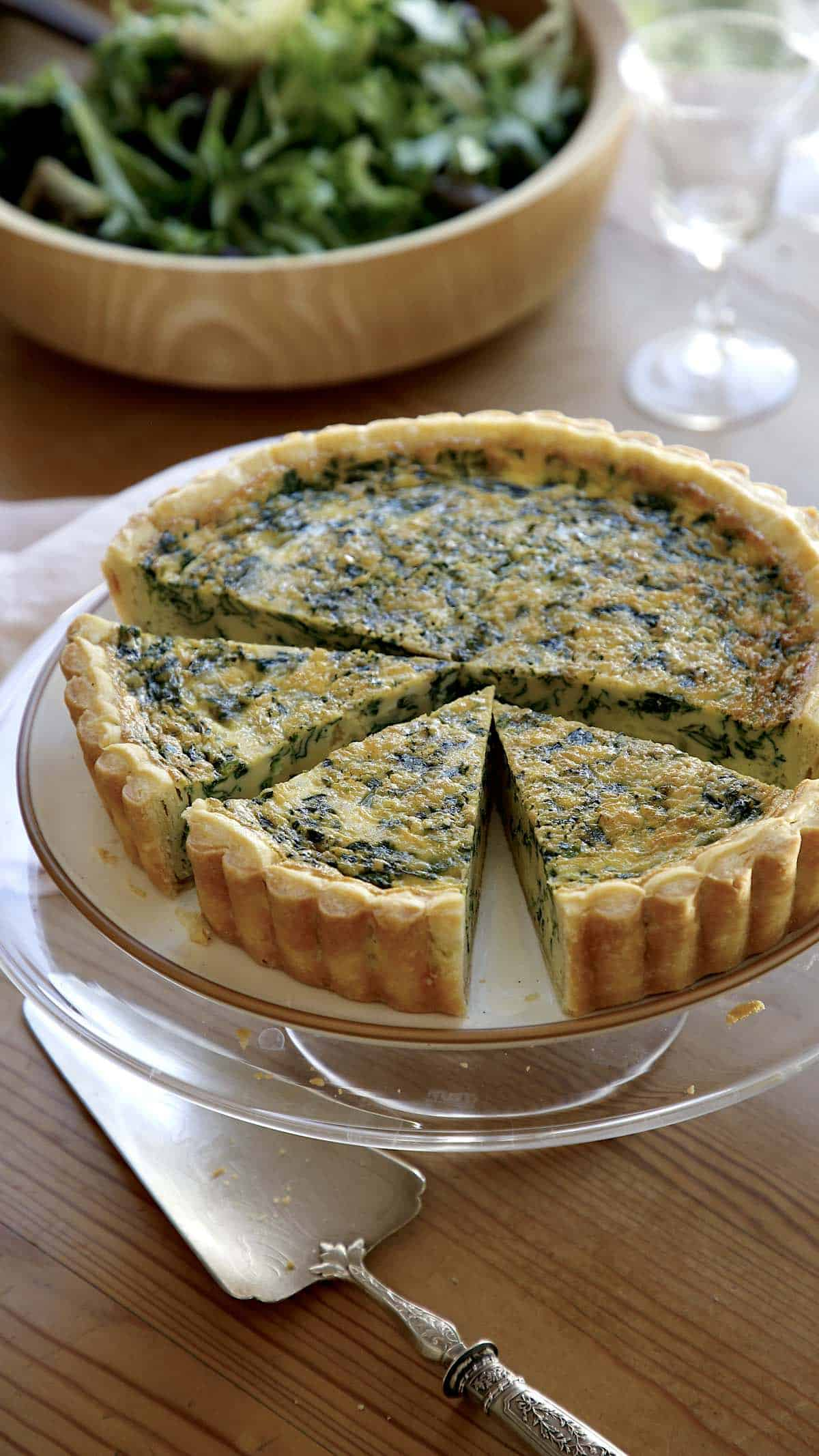 Spinach Quiche on a cake stand with slices cut and a salad bowl
