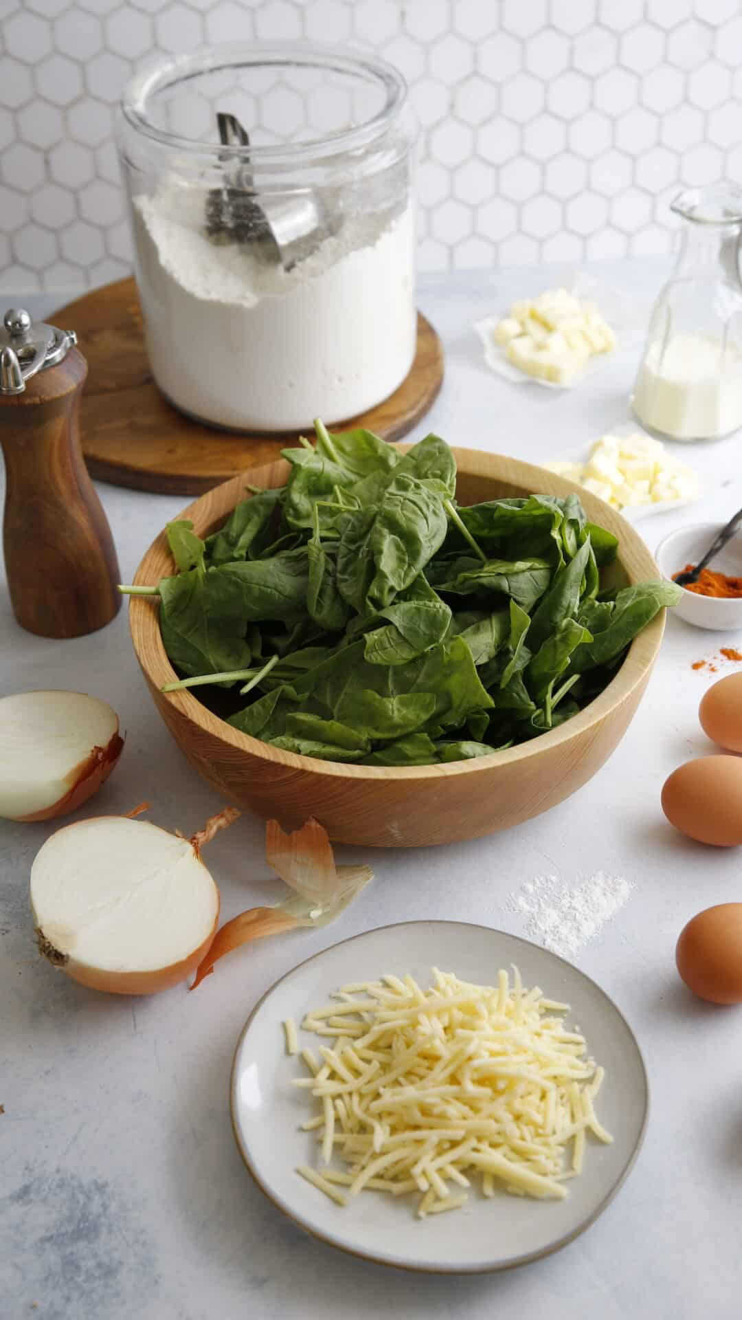 Ingredients on a table including spinach, eggs, cream, cheese and onions