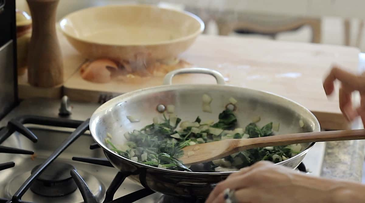 sautéing spinach and onions in a pan
