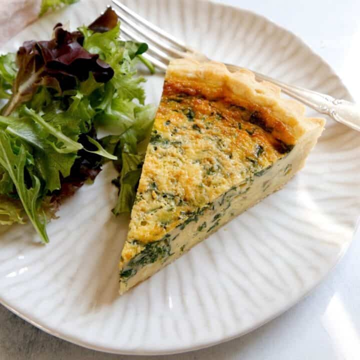 Slice of Spinach Quiche on a Plate with Salad