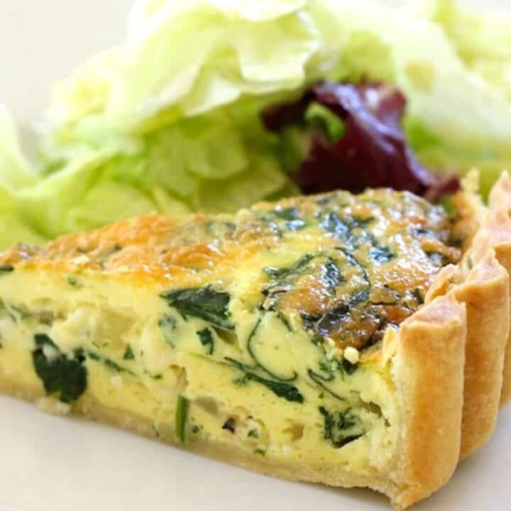 a slice of spinach quiche with a side salad