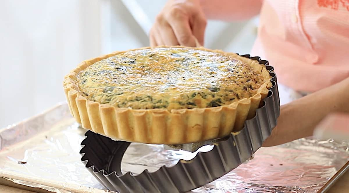 a person removing a baked quiche from a removable bottom quiche pan