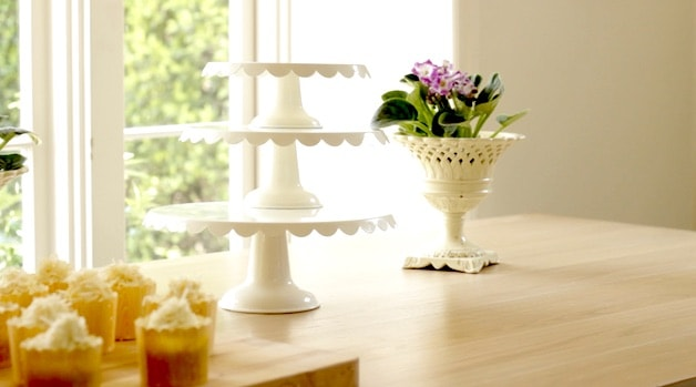 3 white cake stands stacked on each other on a table