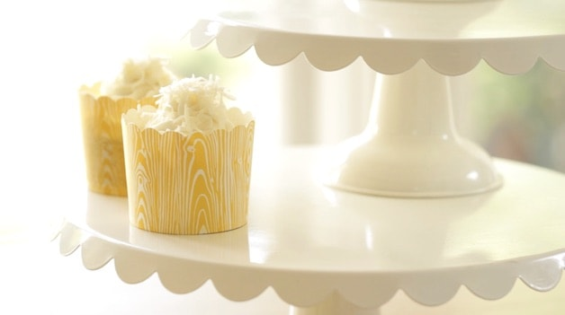 Banana Cupcake in yellow cupcake holder topped with coconut on a cake stand