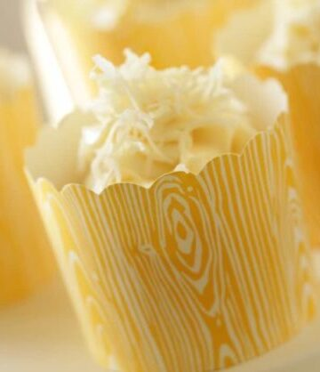 Banana Coconut Cupcake served in a yellow paper cup on a white cake stand