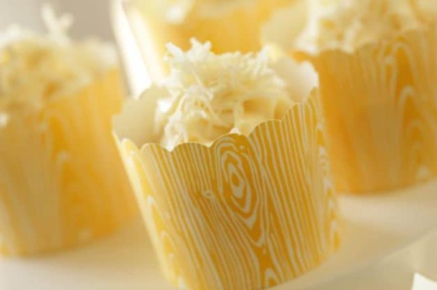 Banana Coconut Cupcake recipe served in a yellow paper cup on a white cake stand