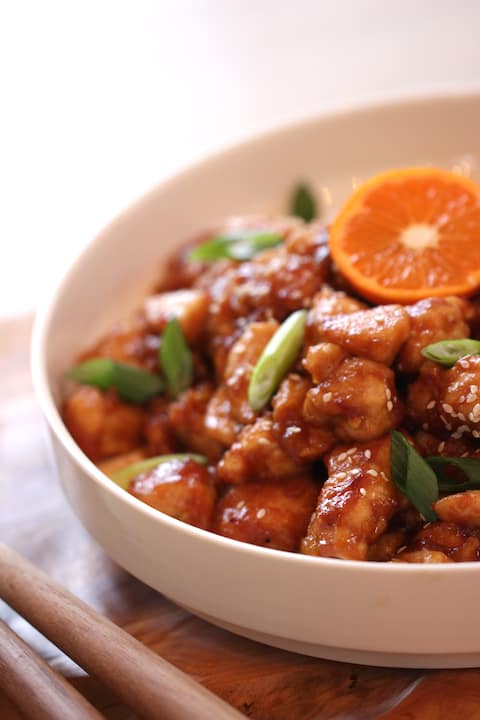 How to Make Orange Chicken recipe served in a white bowl garnished with citrus