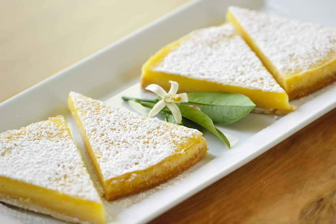 Lemon Bar Pie sliced into triangles and put on a white plate with a lemon blossom