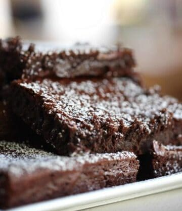 Fudgy Brownies cut into squares and stacked on a white platter