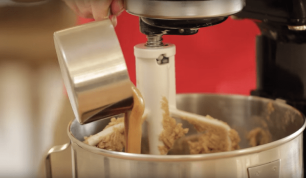 peanut butter being poured into butter and sugar mixture for the best peanut butter cookie recipe