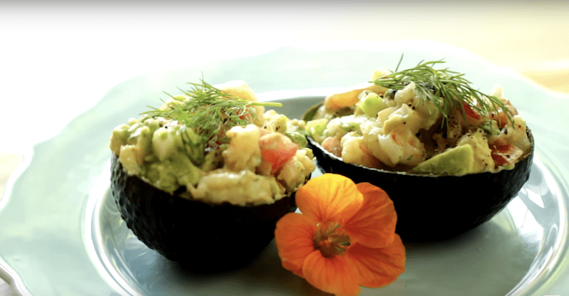 Avocado Shrimp Salad Cups served on a blue plate with orange flower