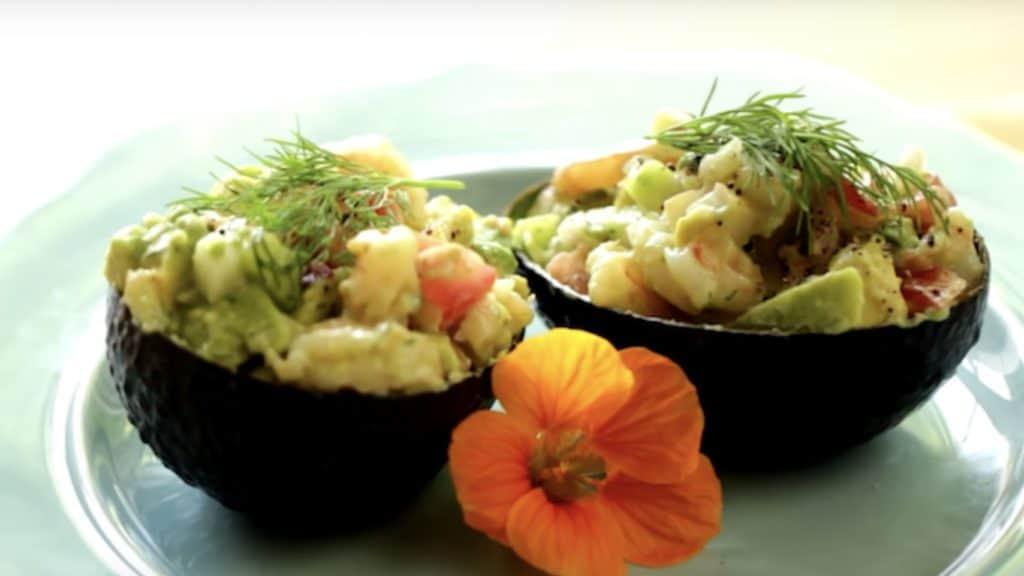 Avocado Shrimp Salad Cups served on a blue plate with orange flower