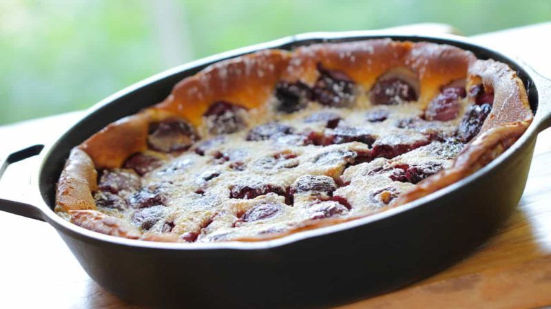 The Best Cherry Clafoutis Recipe baked and cooling in a cast iron skillet