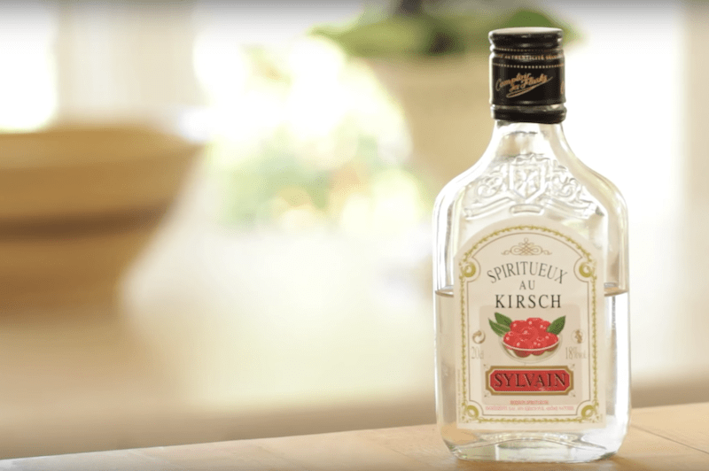 kirsch bottle sitting on wood counter ready to be used in The Best Cherry Clafoutis Recipe
