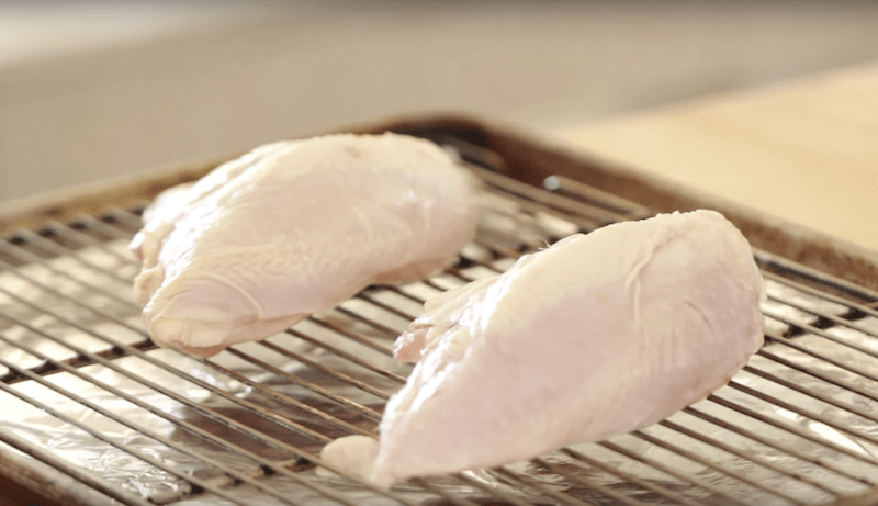 raw chicken breasts on a rack on a sheet pan for BBQ Chicken Slider Recipe