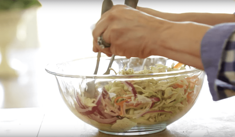 coleslaw being mixed together with two forks in a clear bowl BBQ Chicken Slider Recipe