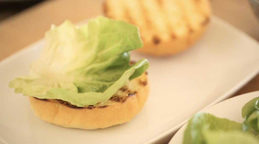 bibb lettuce being stacked on top of a brioche bun on a white plate for an ultimate burger recipe