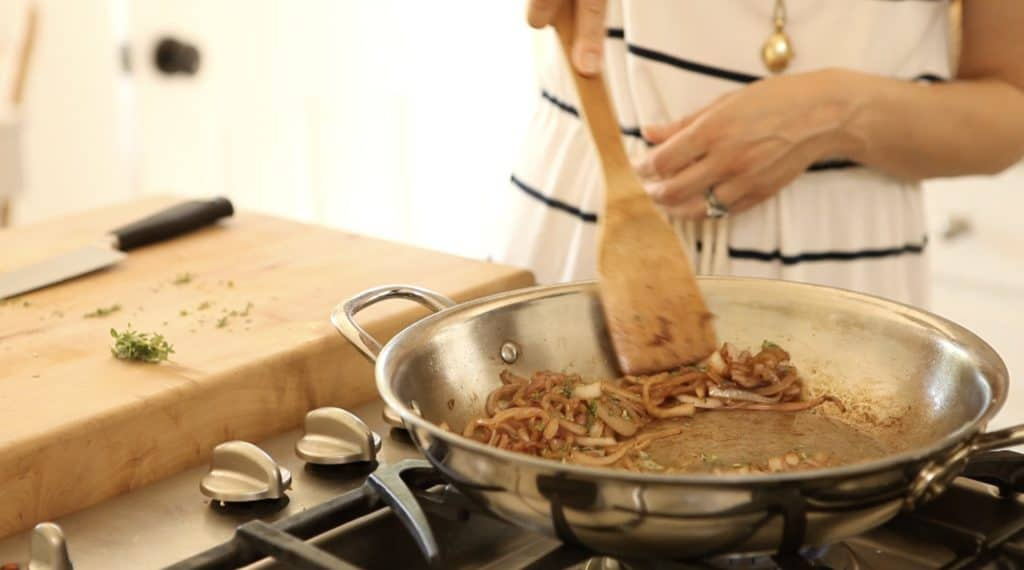 onions being caramelized in a stainless steel pan with a wooden spatula over a gas stove for an ultimate burger recipe