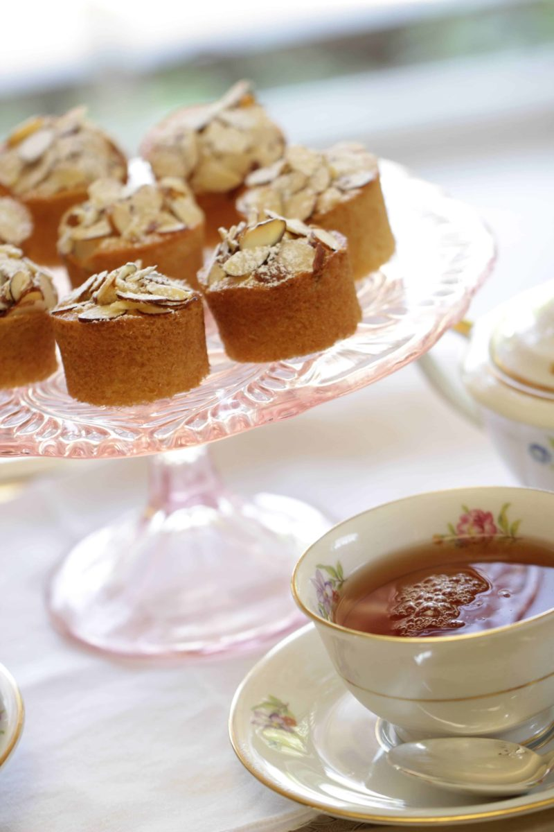 Raspberry Almond Thimble Cakes served on a cake stand with a cup of tea