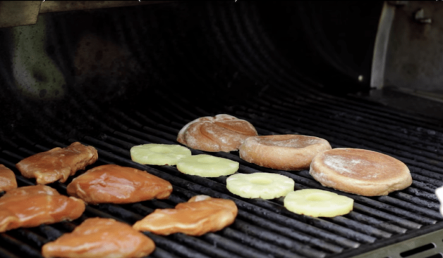 teriyaki chicken, pineapple rings and buns being grilled for a Grilled Chicken Teriyaki Sandwich Recipe