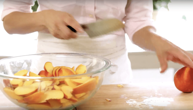 How to Make Peach Cobbler Recipe peaches being sliced on a wood board and added to a clear bowl