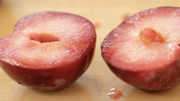 A whole pluot sliced open on a wood cutting board
