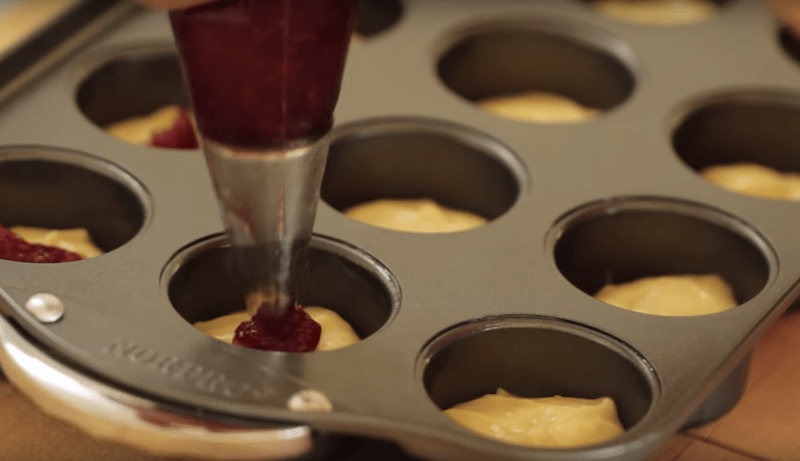raspberry jam being piped into batter of raspberry almond thimble cakes