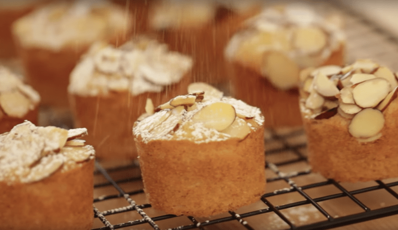 powdered sugar being sprinkled on top of raspberry almond thimble cakes