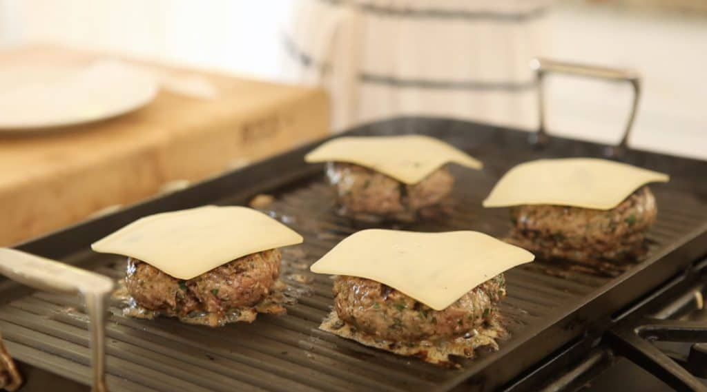 Swiss cheese being melted on burger patties on a grill for an ultimate burger reicpe