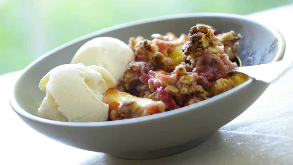 summer fruits crumble recipe served in a large bowl with vanilla ice cream