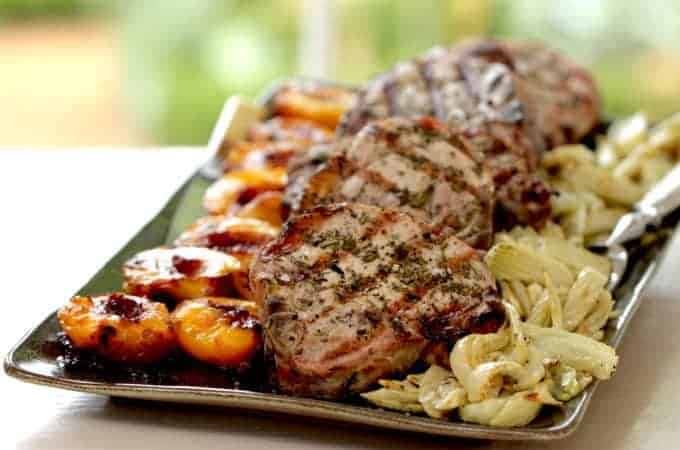 how to grill pork chops recipe served on a large platter with grilled nectarines and roasted fennel
