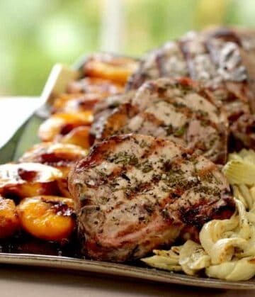 pork chops served on a large platter with grilled nectarines and roasted fennel