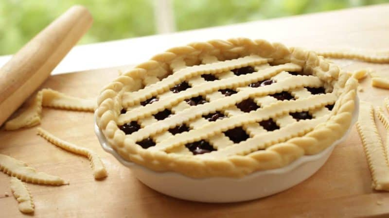 pie unbaked sitting on a wood counter top with a rolling pin and pie dough scraps for a how to make a cherry pie recipe